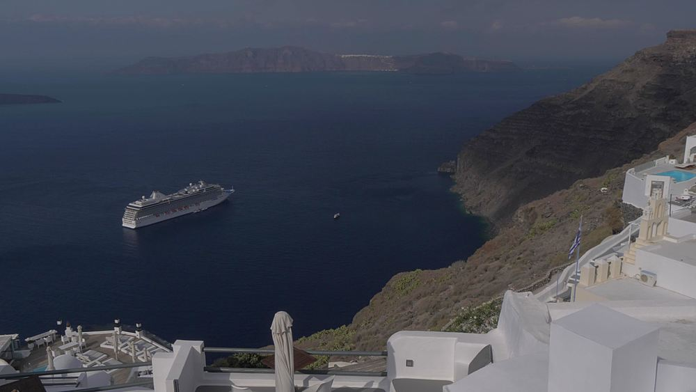 View of white washed villas and cruise ship at Fira, Santorini, Greek Islands, Greece, Europe