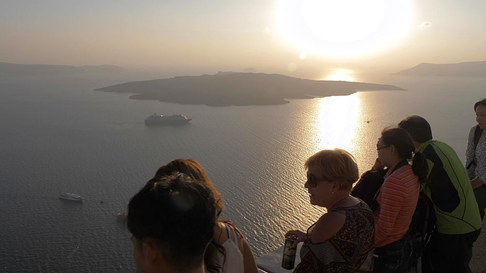 Roaming shot of people viewing sunset and cruise ship moored in Med, Fira, Santorini, Cyclades Islands, Greek Islands, Greece, Europe