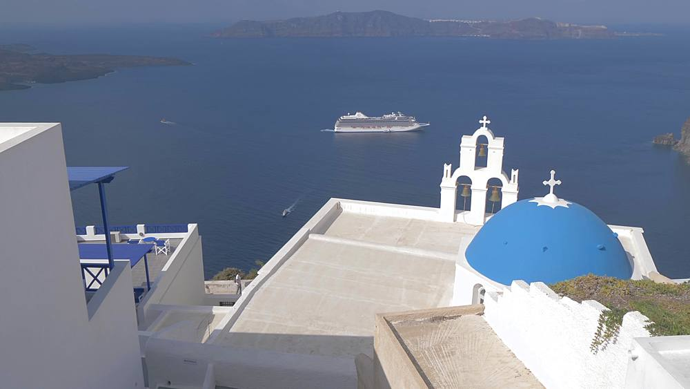 Blue dome and belltower of the church of St. Gerasimos, Firostefani and cruise ship at Fira, Santorini, Greek Islands, Greece, Europe