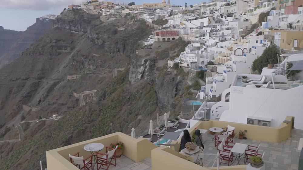 Crane shot of domed churches and whitewashed houses to coastline, Fira, Santorini, Cyclades, Greek Islands, Greece, Europe