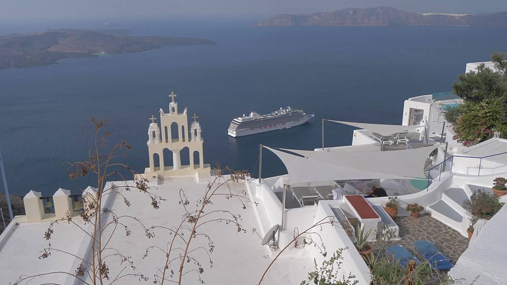 View of white washed villas and cafes and cruise ship at Fira, Santorini, Greek Islands, Greece, Europe