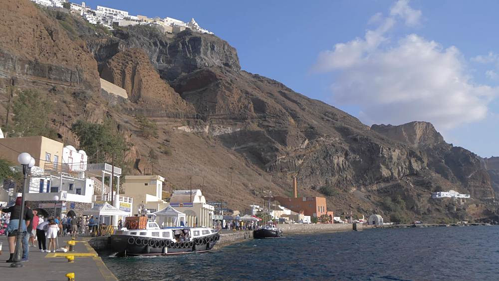 Slider shot of harbour overlooked by Fira town high on cliff, Santorini, Cyclades Islands, Greek Islands, Greece, Europe