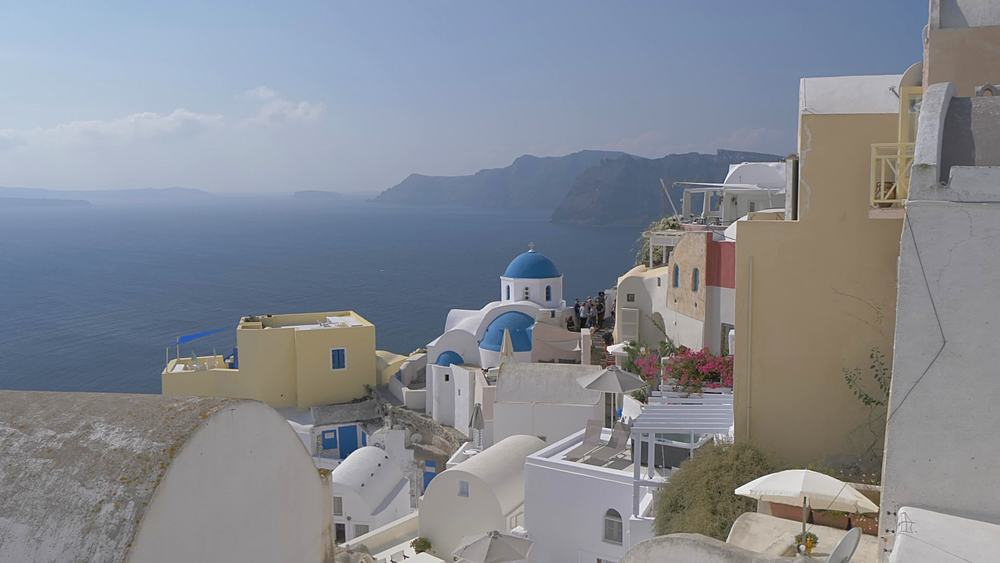 Crane shot of blue domed chapel and Med Sea in Oia overlooking Med Sea, Santorini, Cyclades, Greek Islands, Greece, Europe