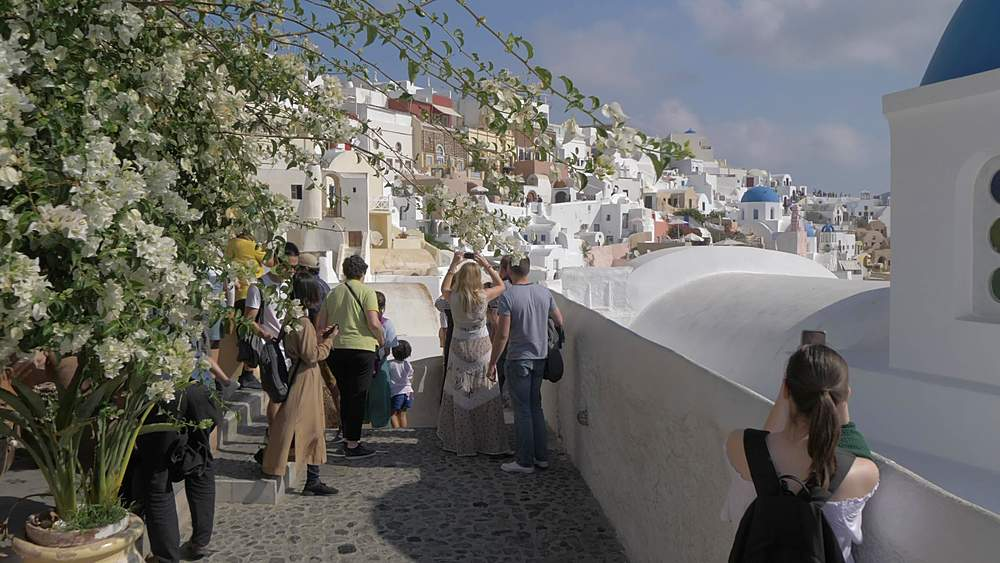 Roaming shot along path through village of Oia towards blue domed chapel, Santorini, Cyclades, Greek Islands, Greece, Europe