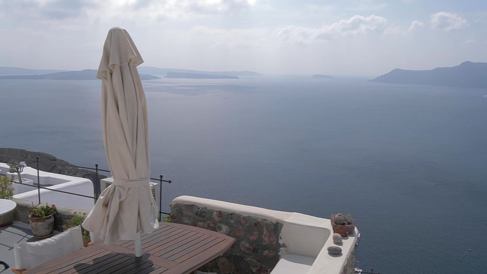 Crane shot of white washed houses and Med Sea in village of Oia, Santorini, Cyclades, Greek Islands, Greece, Europe