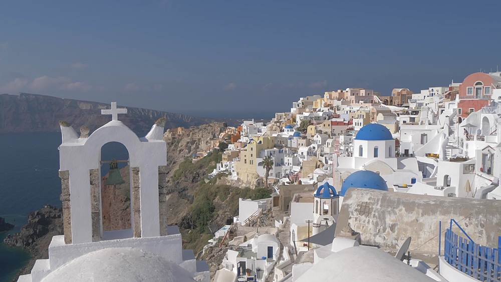 Crane shot of white washed houses and blue domed chapels in Oia, Santorini, Cyclades, Greek Islands, Greece, Europe
