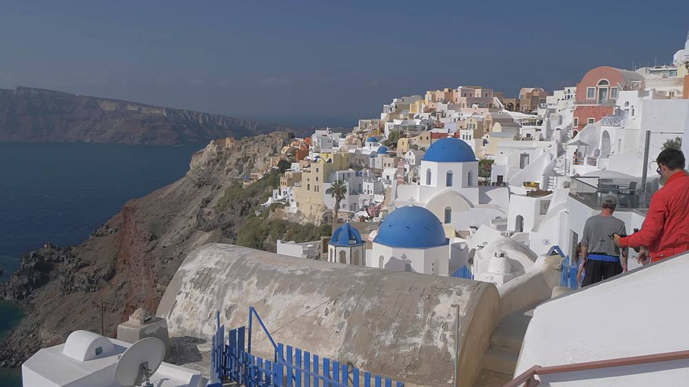 Panning shot of white washed houses and blue domed chapels in Oia, Santorini, Cyclades, Greek Islands, Greece, Europe