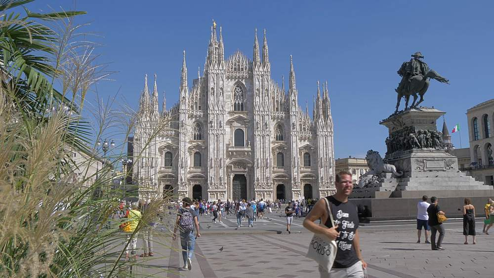 Tracking shot of people and Duomo in Piazza del Duomo, Milan, Lombardy, Italy, Europe