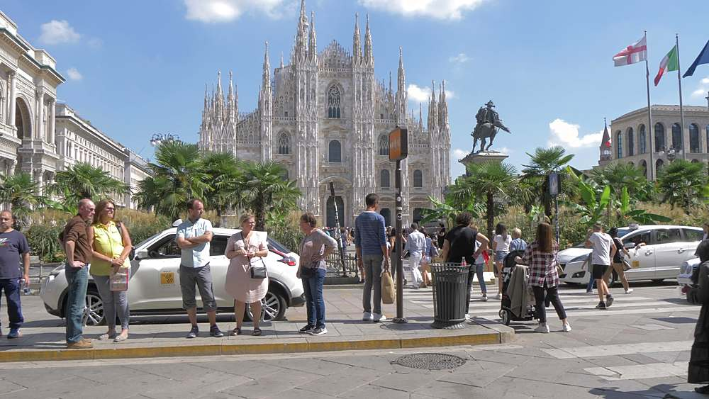Tracking shot of people, restaurants, cars and the Duomo in Piazza del Duomo, Milan, Lombardy, Italy, Europe