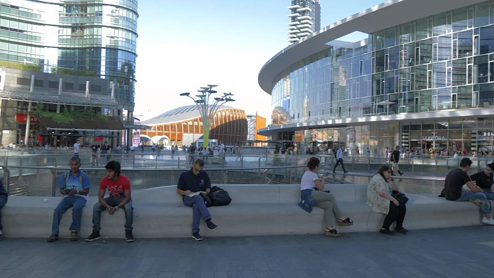 Panning shot of people in Piazza Gae Aulenti modern architecture, Milan, Lombardy, Italy, Europe