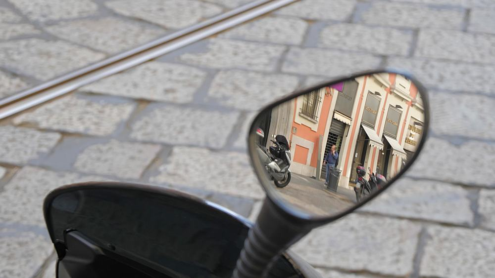 Traffic and people in mirror of motorcycle on Via Alessandro Mansoni in Milan, Milan, Lombardy, Italy, Europe
