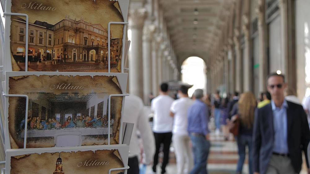 View of postcards and people out of focus in Piazza del Duomo, Milan, Lombardy, Italy, Europe
