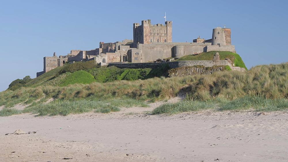 Panning shot of Bamburgh Beach to Bamburgh Castle, Northumberland, England, United Kingdom, Europe
