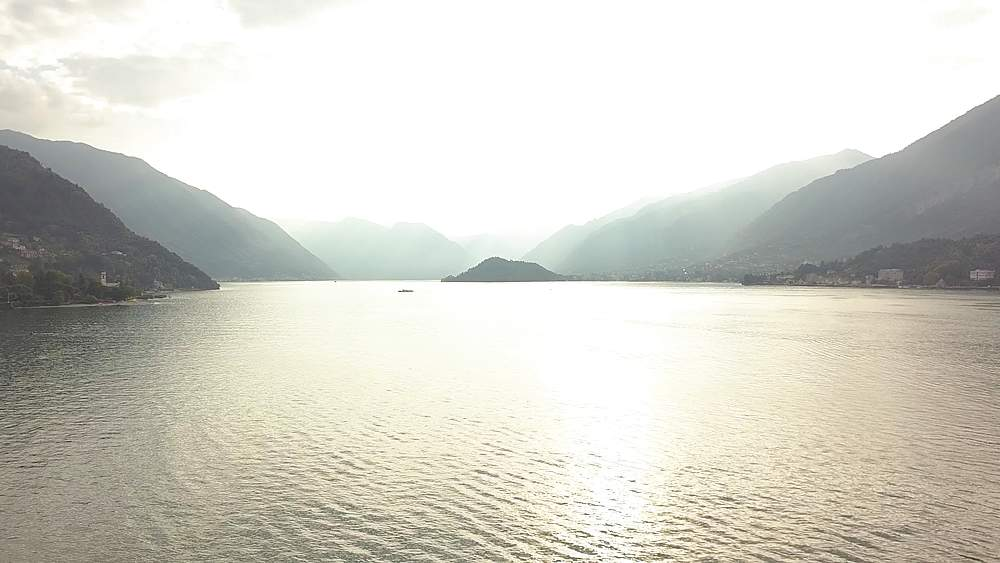Panning flight over Lake Como into sunlight near lakeside town of Bellagio, Lombardy, Italy, Europe - 844-18799