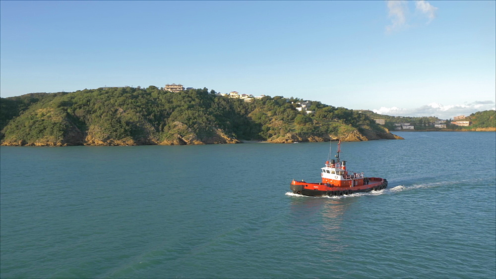 Shot of tug boat guiding cruise ship into St. John's from moving cruise ship, Antigua, Antigua and Barbuda, Caribbean Sea, West Indies, Caribbean, Central America