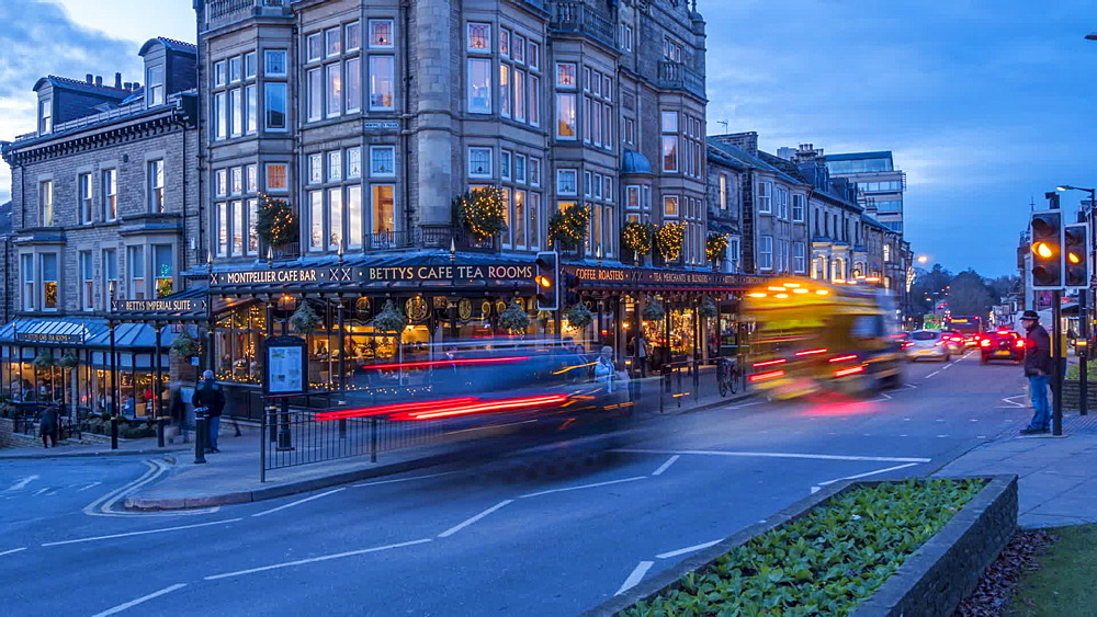 Time Lapse of people and traffic at Betty's Tea Rooms at dusk, Harrogate, North Yorkshire, England, United Kingdom, Europe