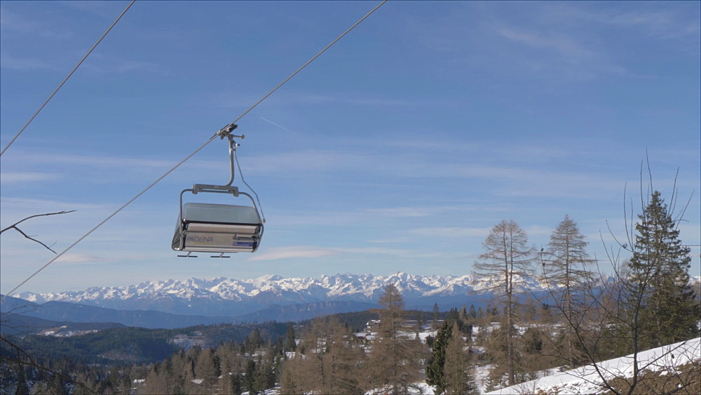 View of ski chairs and mountains in background at Carezza, Province of Trento, Trentino-Alto Adige/Sudtirol, Italy, Europe