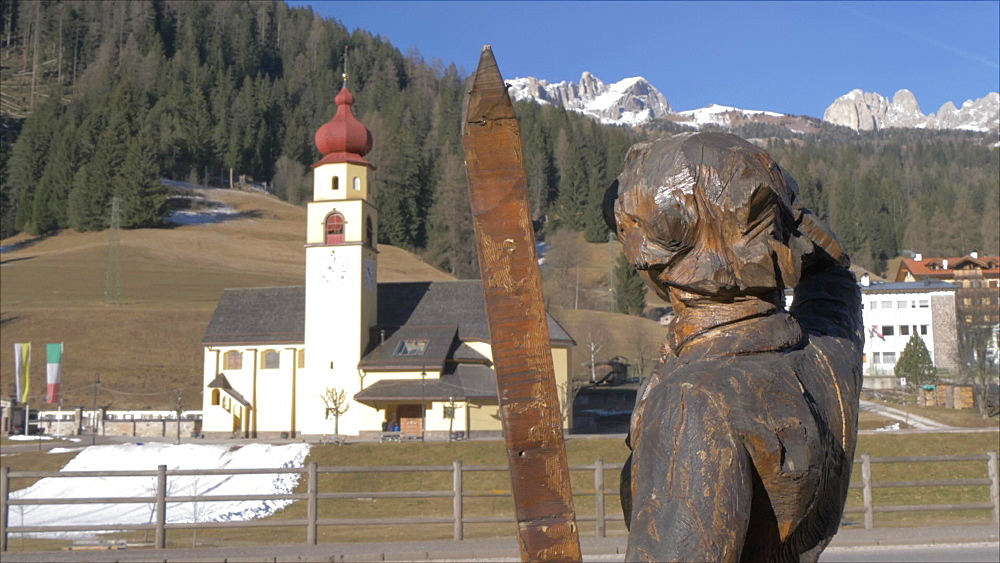 View of symbolic skier and church in Soraga on sunny day in winter, Province of Trento, Italian Dolomites, Italy, Europe