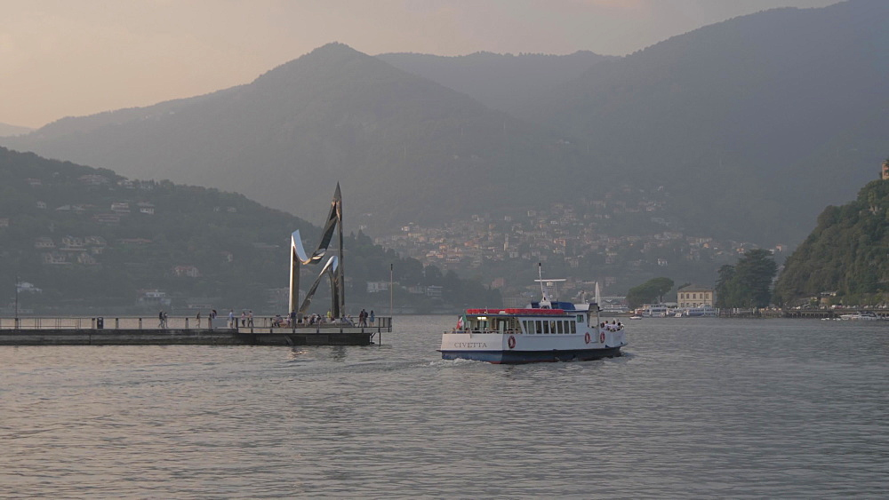 View of boat leaving harbour at Como at sunset, Lake Como, Lombardy, Italian Lakes, Italy, Europe