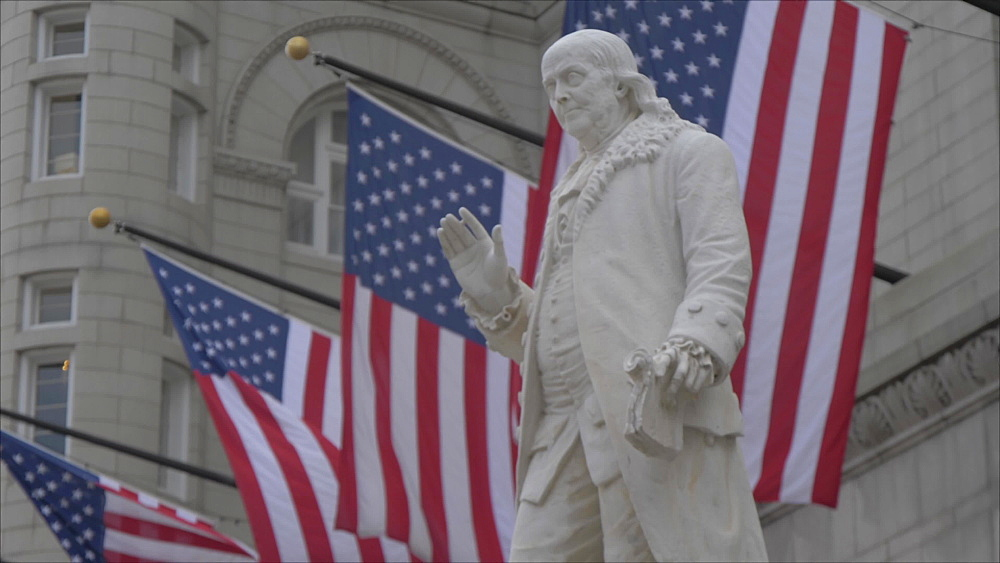 Tilt shot of Benjamin Franklin statue and US flags in front of former Old Post Office Pavilion, Washington DC, District of Columbia, USA