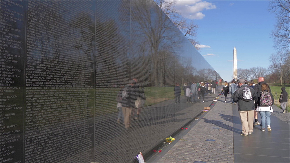 Pan shot of Vietnam Veterans Memorial, people and Washington Monument, Washington DC, District of Columbia, USA, North America