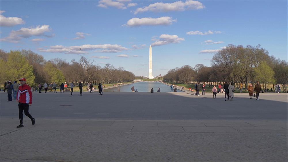 Low traversing shot of people, Washington Monument on National Mall at sunset, Washington DC, District of Columbia, USA, North America