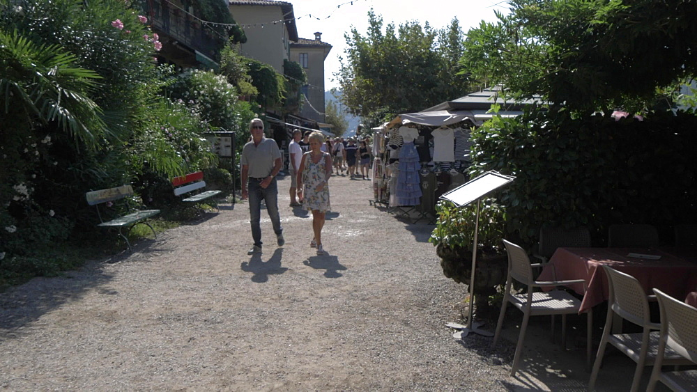 Roaming shot of people and cafes on Isola dei Pescatori, Lake Maggiore, Piedmont, Italian Lakes, Italy, Europe