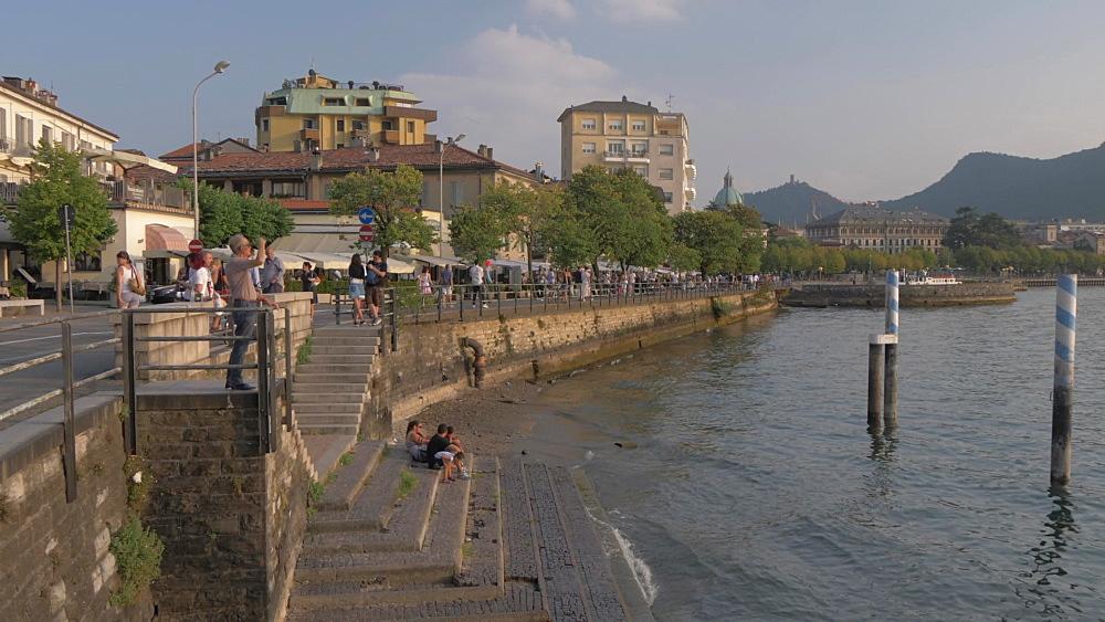 Pan shot of people on lakeside walk in Como town, Como, Lake Como, Lombardy, Italian Lakes, Italy, Europe