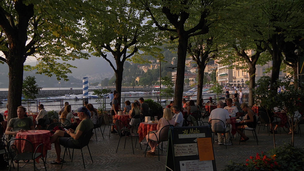 Restaurant on lakeside in Como town at sunset, Como, Lake Como, Lombardy, Italian Lakes, Italy, Europe