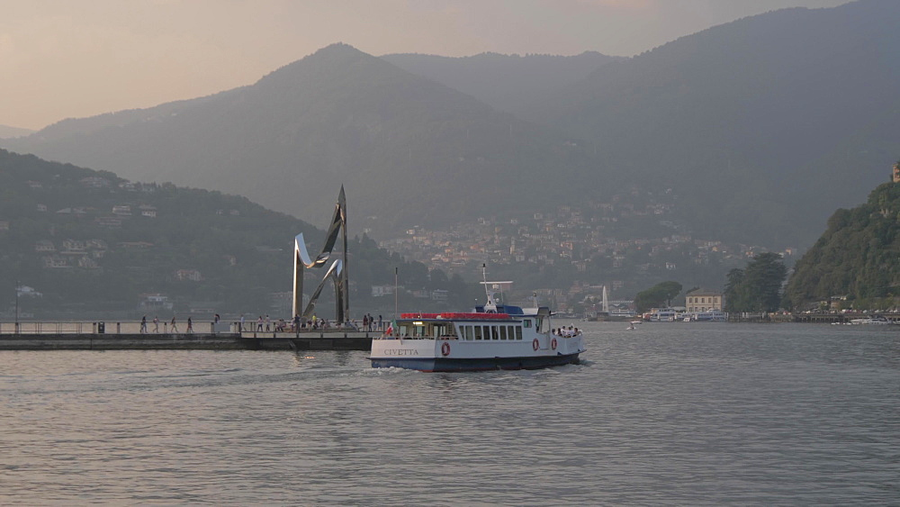 Boat leaving harbour in Como town at sunset, Como, Lake Como, Lombardy, Italian Lakes, Italy, Europe