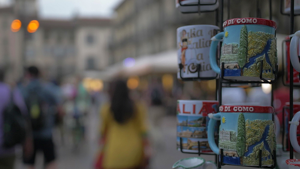 People and souvenir mugs in Piazza del Duomo at dusk, Como, Lake Como, Lombardy, Italian Lakes, Italy, Europe