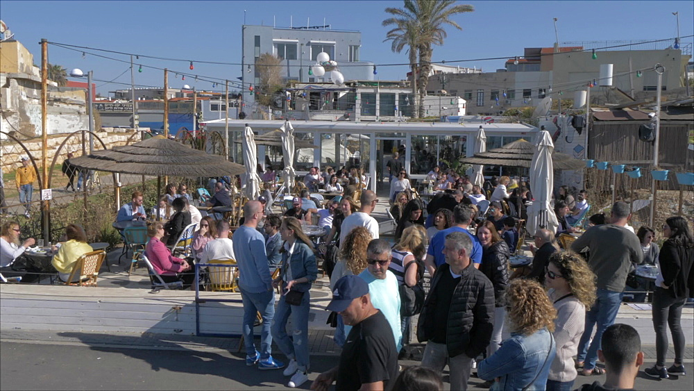 Busy restaurant and promenade and city backdrop, Tel Aviv, Israel, Middle East