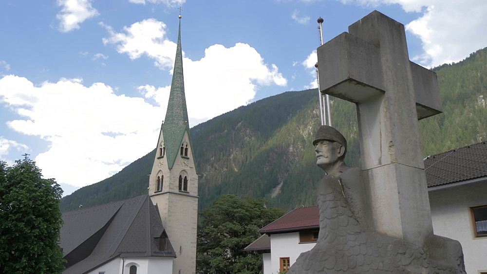 War memorial statue and church, Mayrhofen, Tyrol, Austrian Alps, Austria, Europe