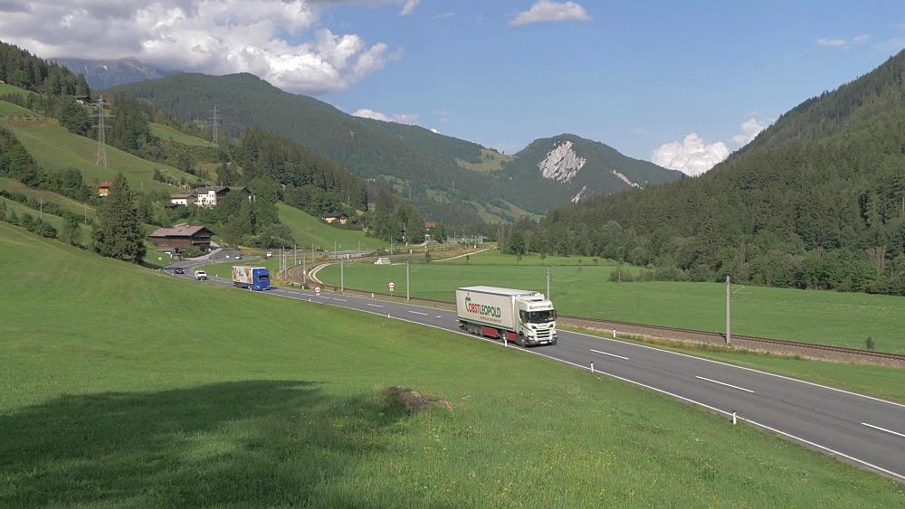 Traffic on busy road with mountainous backdrop near Mandling, Styria, Austrian Alps, Austria, Europe