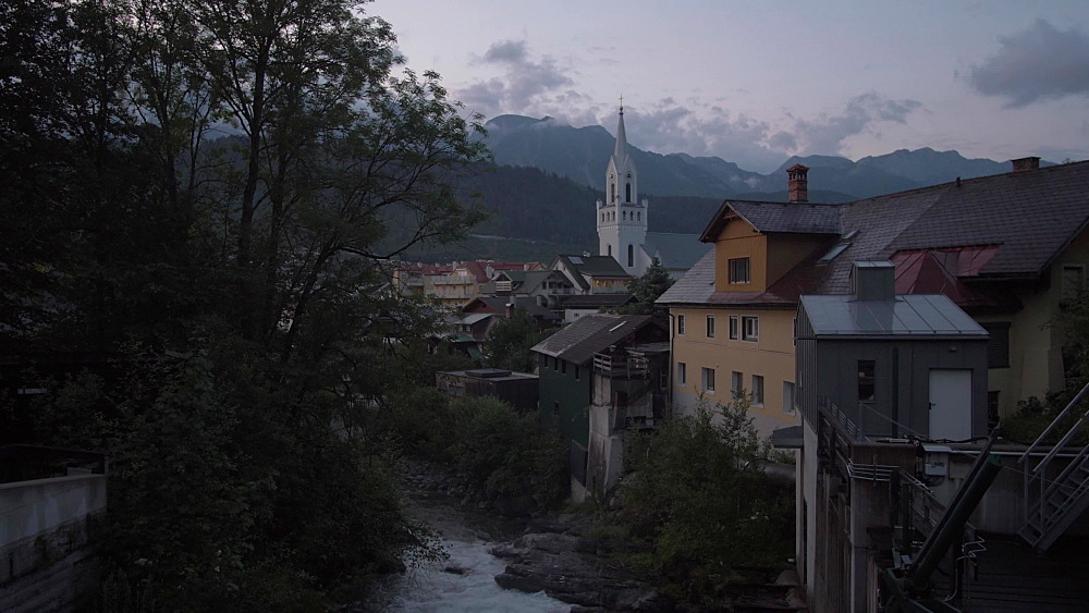 Shot from river to traditional buildings and Evangelist Church at dusk, Schladming, Styria, Austrian Alps, Austria, Europe
