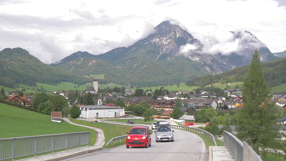 Busy road and the town of Grobming, Styria, Austrian Alps, Austria, Europe