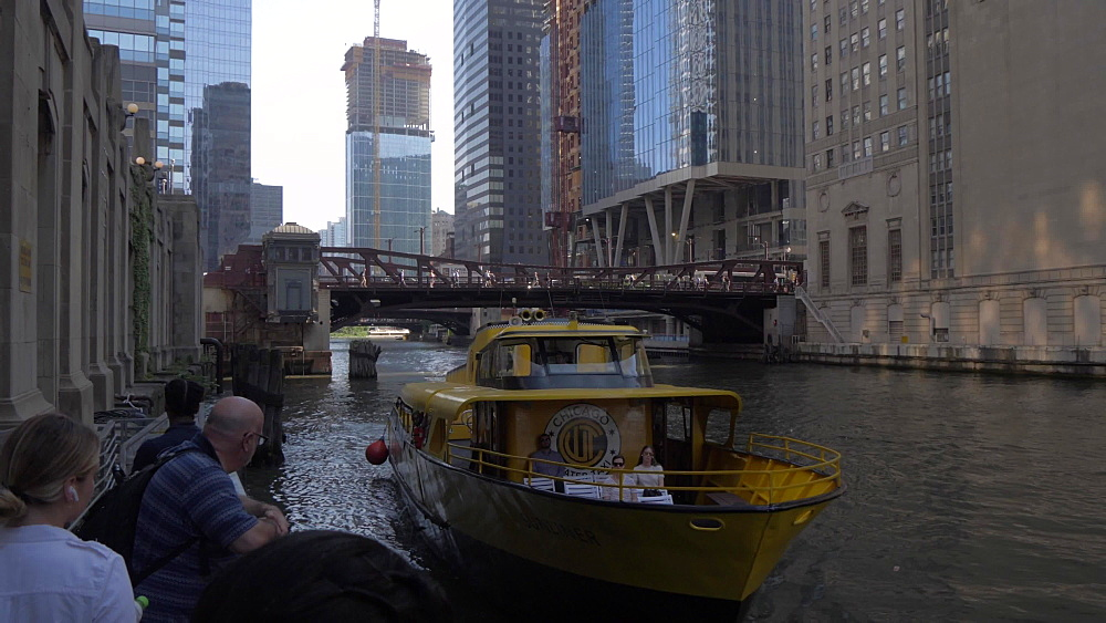 River taxi arriving at terminal and tall buildings from Chicago River, Chicago, Illinois, United States of America, North America