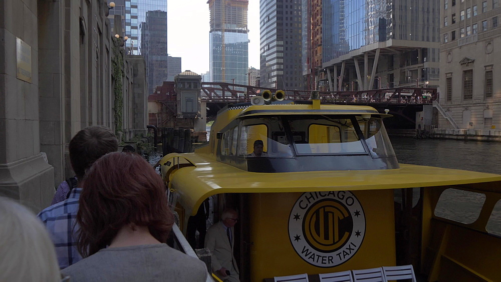 People boarding river taxi and tall buildings from Chicago River, Chicago, Illinois, United States of America, North America