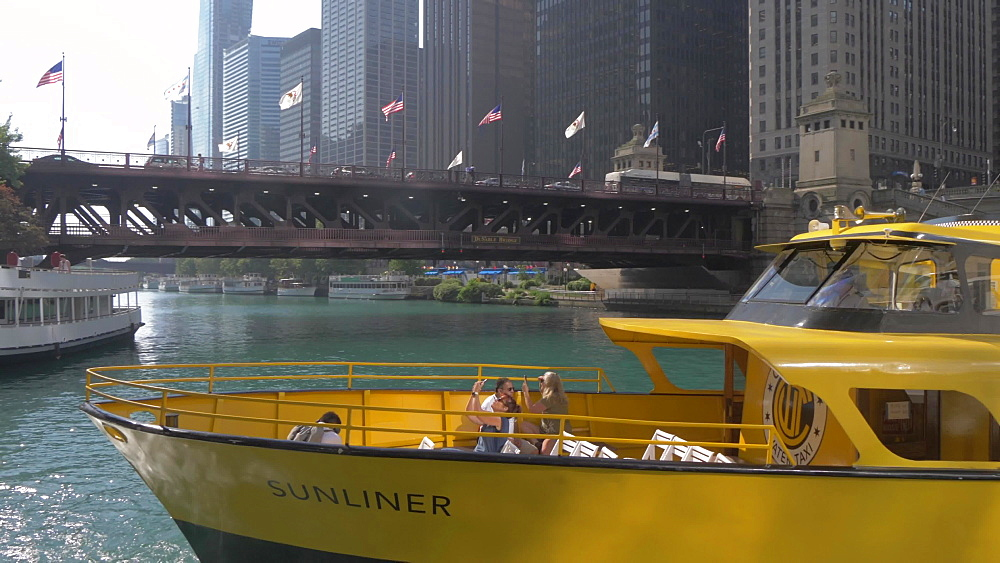 River taxi leaving terminal on Chicago River and tall buildings, Chicago, Illinois, United States of America, North America