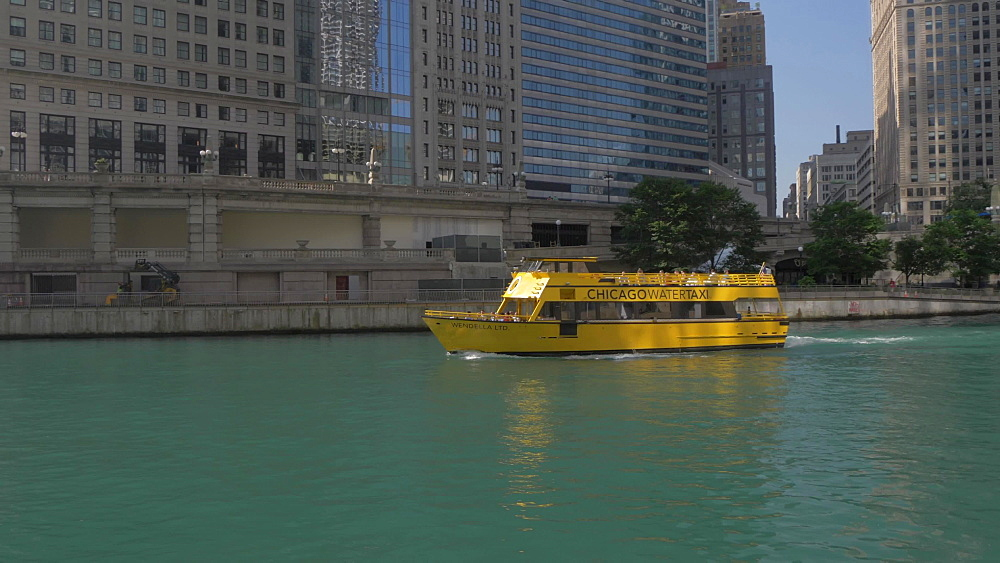 Water taxi on Chicago River and tall buildings, Chicago, Illinois, United States of America, North America
