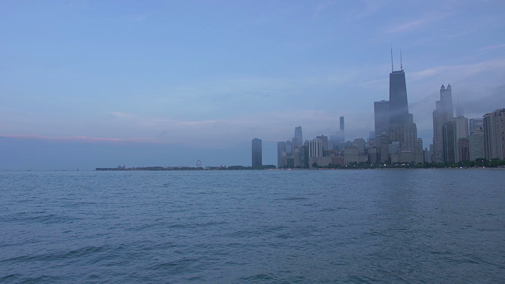 Fog coming in from Michigan Lake to city skyline from Lakefront Trail at dusk, Chicago, Illinois, United States of America, North America