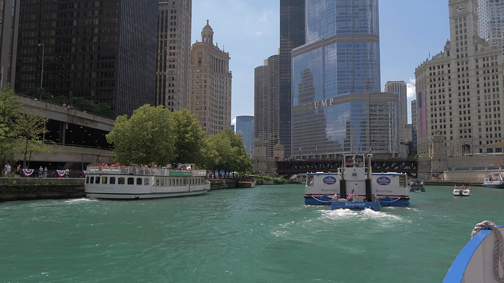 Onboard cruise boat shot tracking another cruise boat and buildings lining the Chicago River, Chicago, Illinois, United States of America, North America