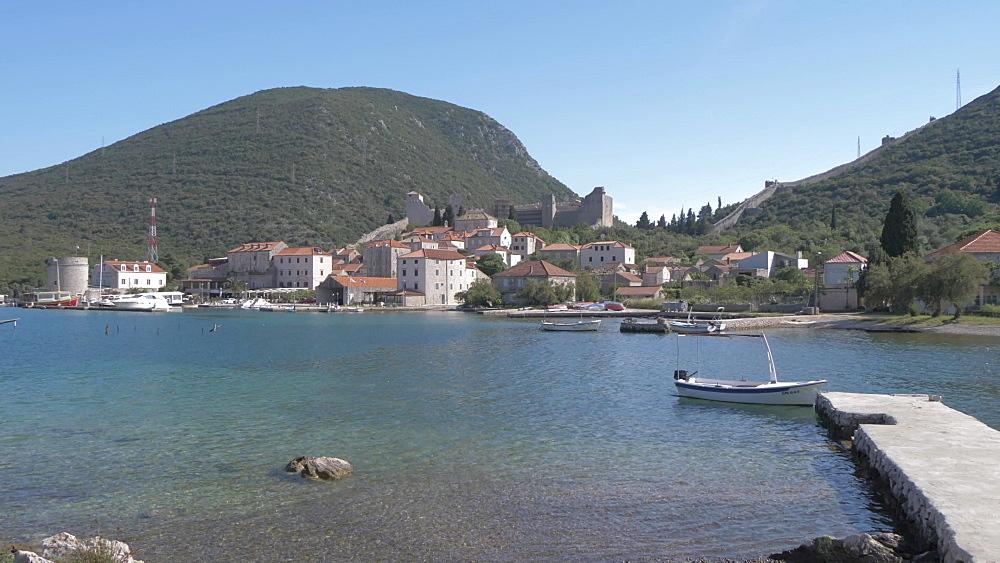 Stony beach, harbour, boats and the village of Mali Ston, Dubrovnik-Neretva, Croatia, Europe