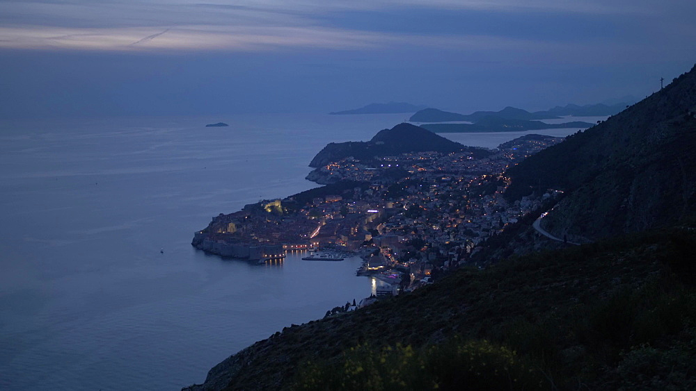 Pan shot of Dubrovnik Old Town and Harbour and Adriatic Sea at dusk, Dubrovnik Riviera, Croatia, Europe