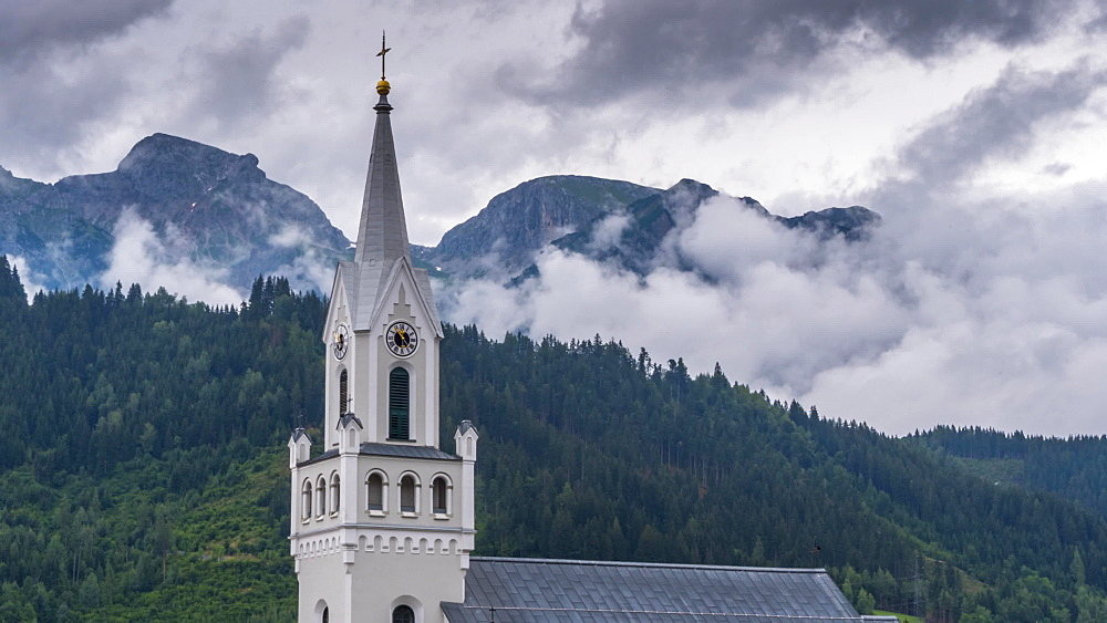 Time lapse of clouds forming and mountainous backdrop to church steeple, Schladming, Styria, Austrian Alps, Austria, Europe
