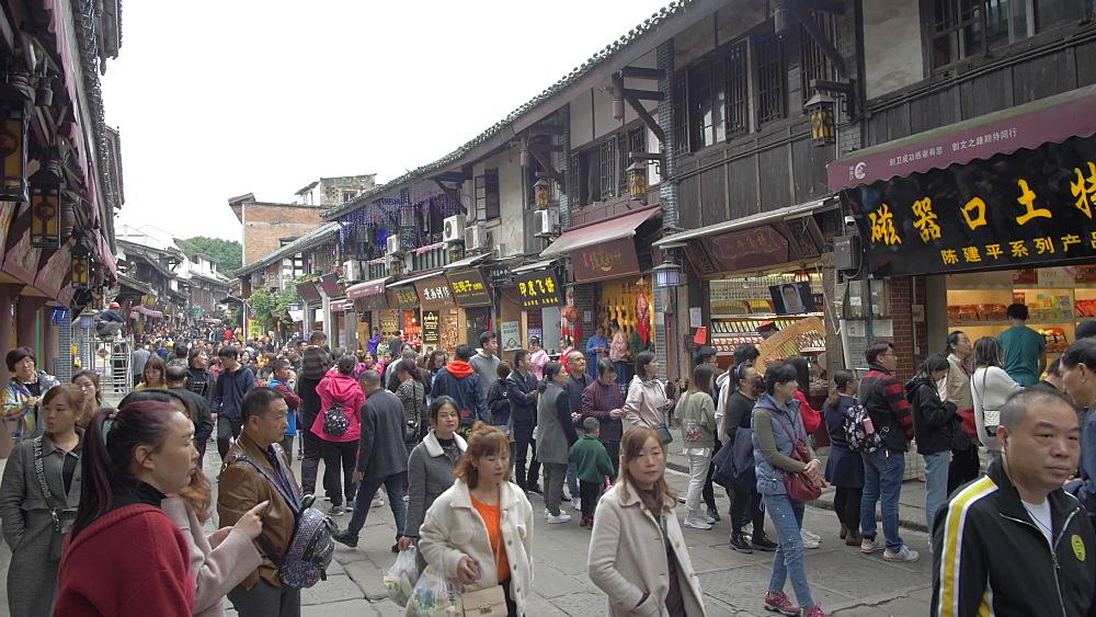Pan shot of street sign and busy shopping street in Ciqikou Old Town, Shapingba, Chongqing, China, Asia
