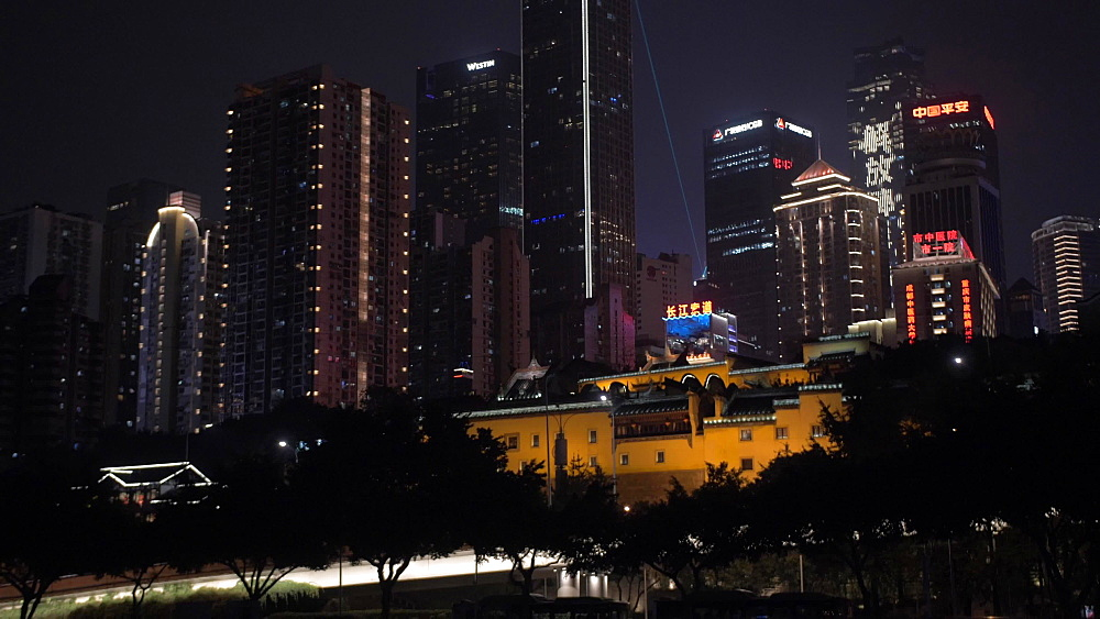Pan shot of cable car and city skyline at night on Yangtze River in Chongqing, Yuzhong District, China, Asia