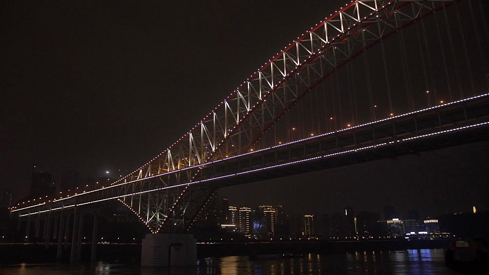 Onboard cruise boat shot of city skyline and illuminated bridges at night, Chongqing, Yuzhong District, China, Asia