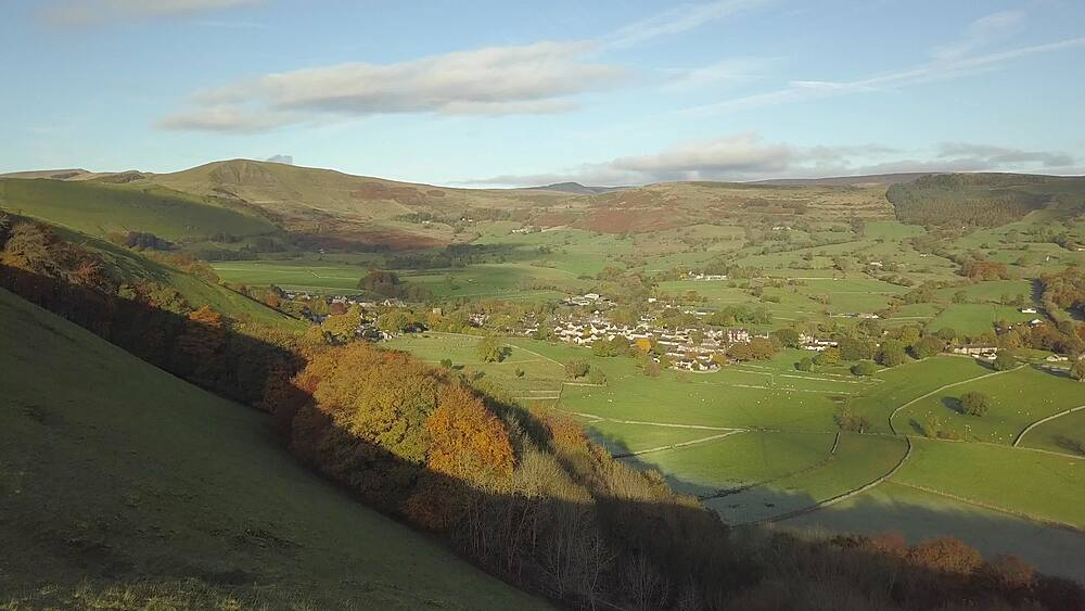 Aerial shot over fields towards Castleton in autumn, Hope Valley, Peak District National Park, Derbyshire, England, United Kingdom, Europe