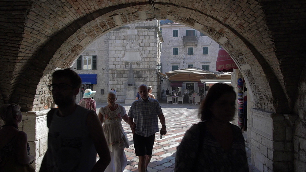 Shot through archway leading to clock tower in Old Town of Kotor, UNESCO World Heritage Site, Montenegro, Europe